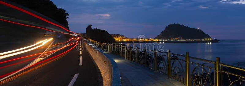 由海的路有汽车的在晚上点燃 库存图片