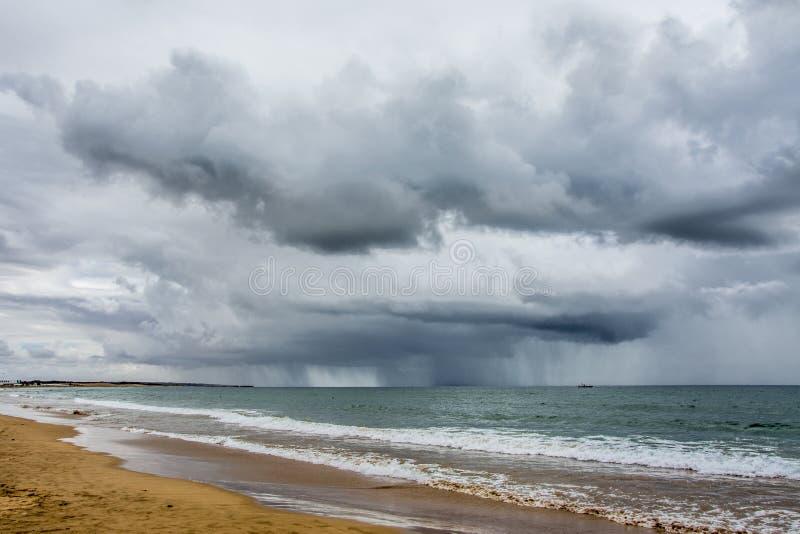 由海的风雨如磐的云彩,海滩 免版税库存图片