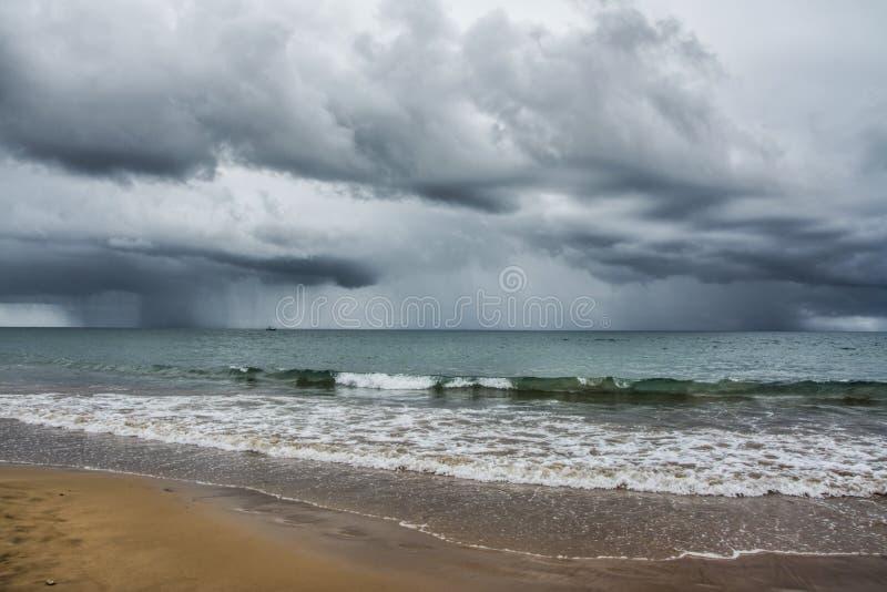 由海的风雨如磐的云彩,海滩 免版税库存照片
