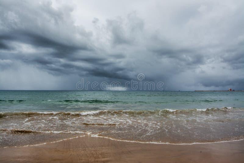由海的风雨如磐的云彩,海滩 库存照片