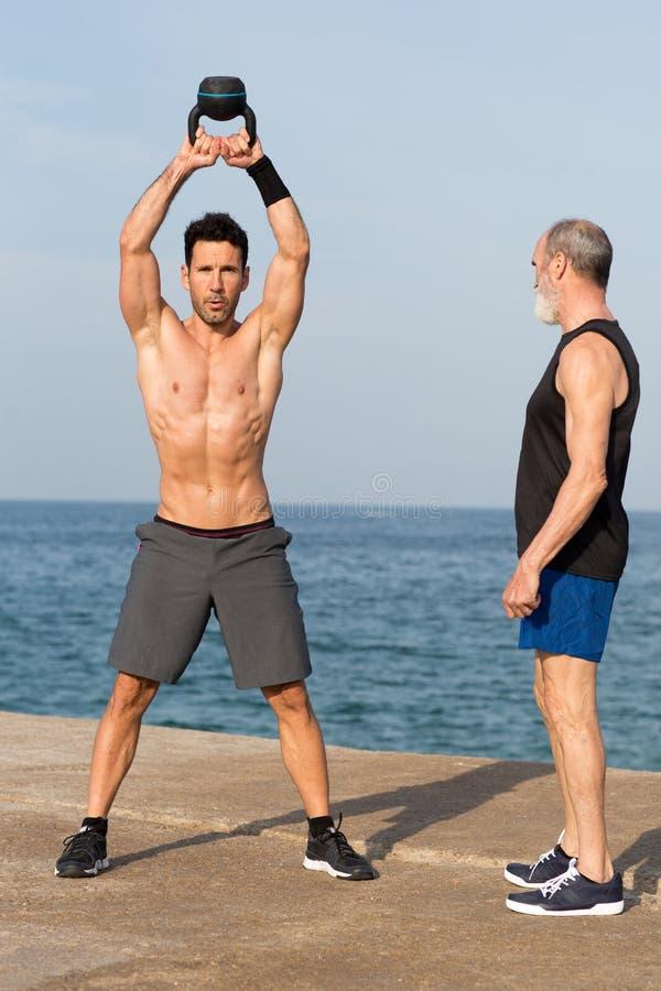 由海的Kettlebell锻炼有教练的 图库摄影