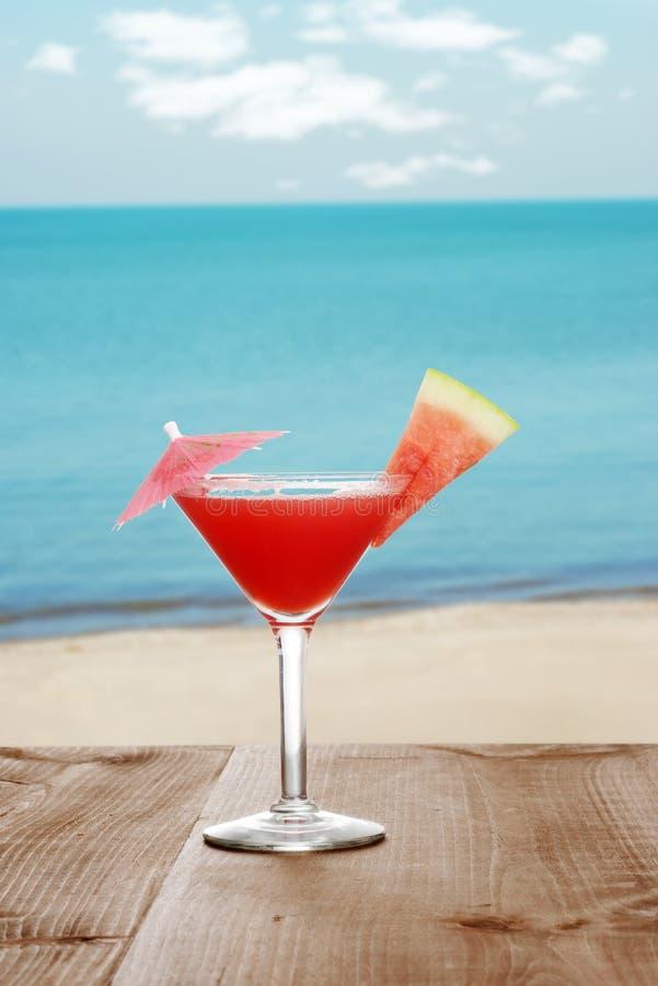 由海滩的西瓜马蒂尼鸡尾酒与果子切片 免版税库存照片