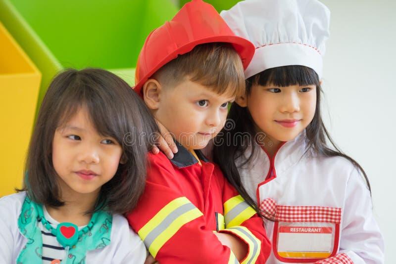 由消防员决定的三个孩子礼服和医生和厨师卷戏剧教室的,幼儿园幼儿教育概念 免版税库存照片