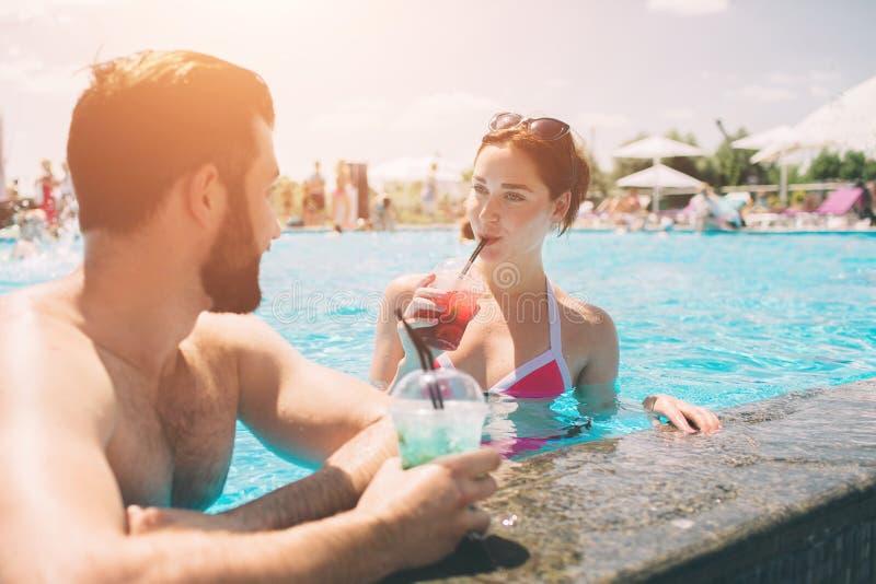 由游泳池的年轻夫妇 男人和妇女在水中的喝鸡尾酒 免版税图库摄影