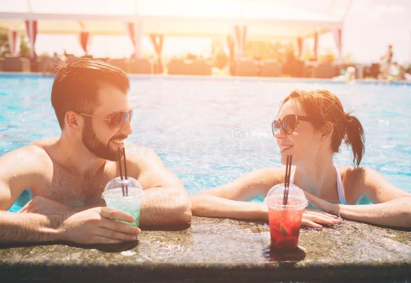 由游泳池的年轻夫妇 男人和妇女在水中的喝鸡尾酒 库存照片