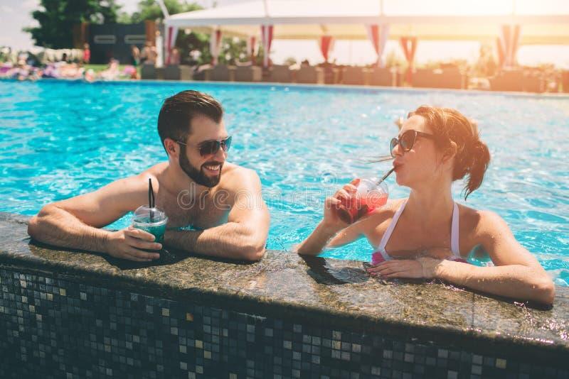 由游泳池的年轻夫妇 男人和妇女在水中的喝鸡尾酒 库存图片