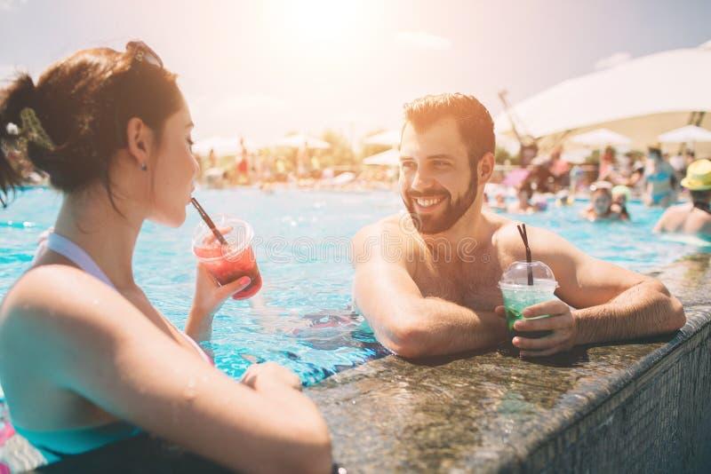 由游泳池的年轻夫妇 男人和妇女在水中的喝鸡尾酒 免版税库存照片