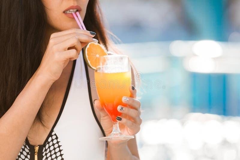 由游泳池的性感的妇女喝鸡尾酒的 图库摄影