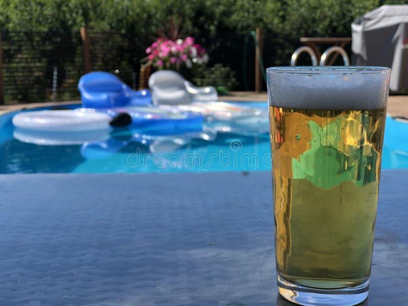 由游泳池边的一个冷的储藏啤酒 库存图片
