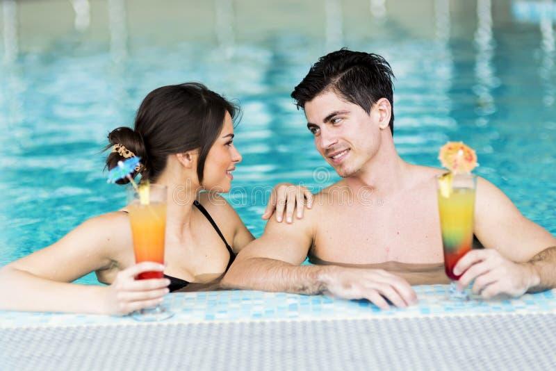 由游泳池结合喝鸡尾酒和放松 免版税库存图片