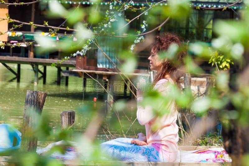 由湖的妇女实践瑜伽室外春天夏日在莲花坐坐用手在anjali mudra 免版税库存照片