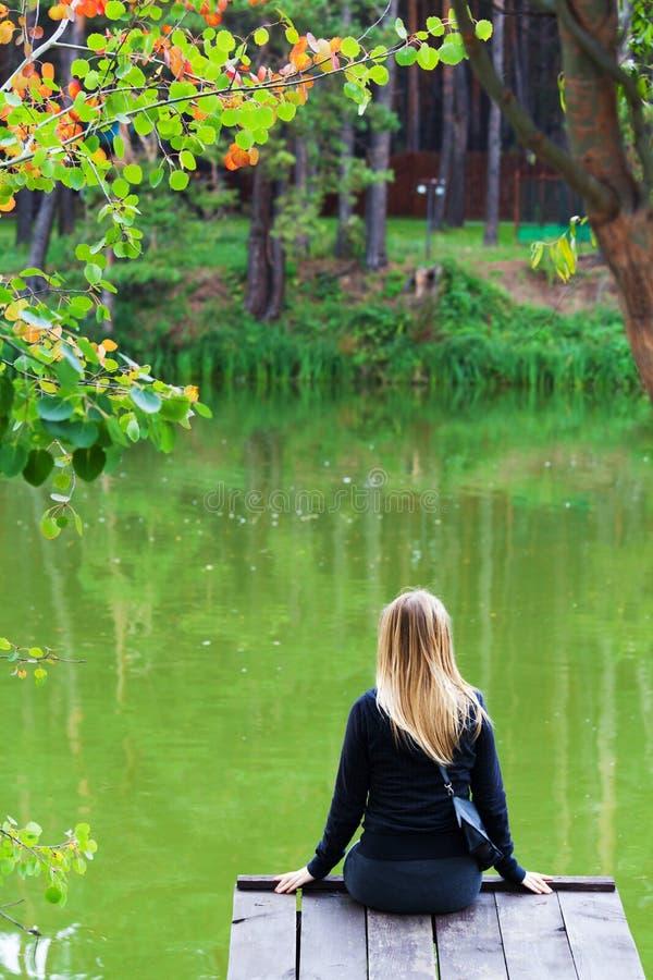 由湖的孤独的女孩在公园 免版税库存图片