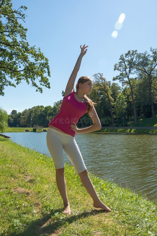 由湖的少妇实践的瑜伽 免版税库存图片