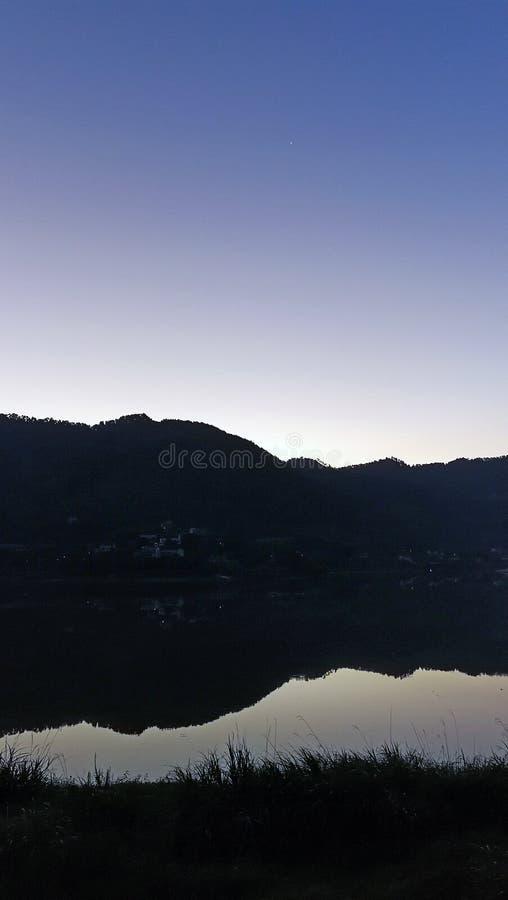 由湖的山与五颜六色的天空的黎明的 免版税库存图片