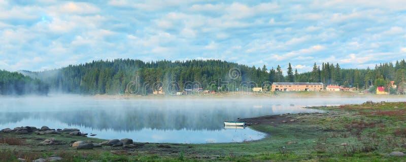 由湖的早晨薄雾,小船,森林 库存图片