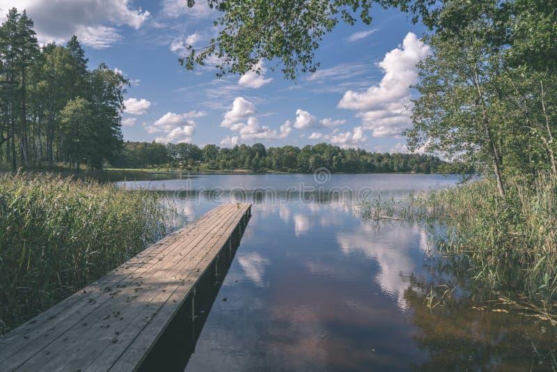 由湖的野餐区有木板条木板走道的-葡萄酒减速火箭的神色 免版税库存照片