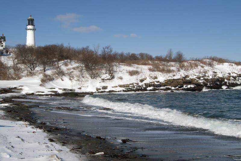 由灯塔的积雪的海滩 免版税库存图片