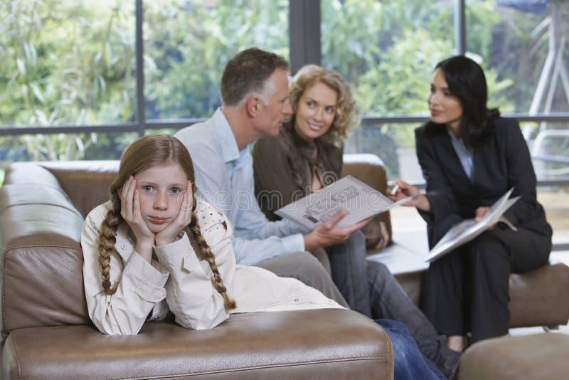 由父母和房地产经纪商的乏味女孩在新的物产 免版税库存图片