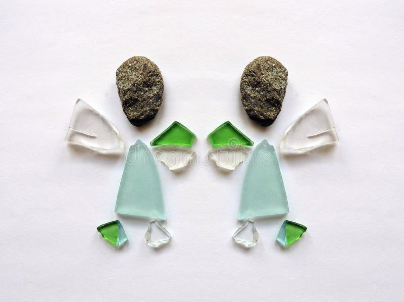 由玻璃片断和石头做的两个天使 图库摄影