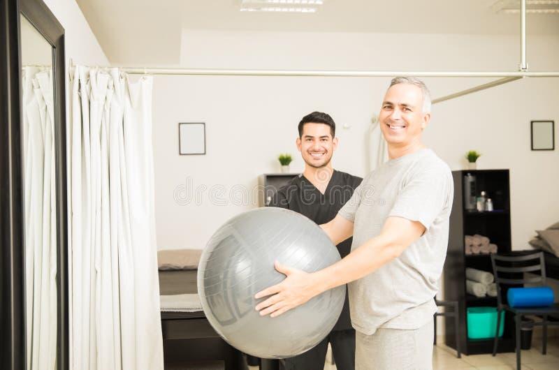 由生理治疗师的耐心举行的锻炼球在医院 库存图片