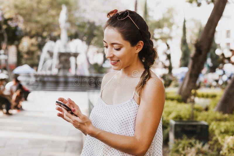 由电话佩带的便服的年轻拉丁妇女传讯在墨西哥 免版税库存照片