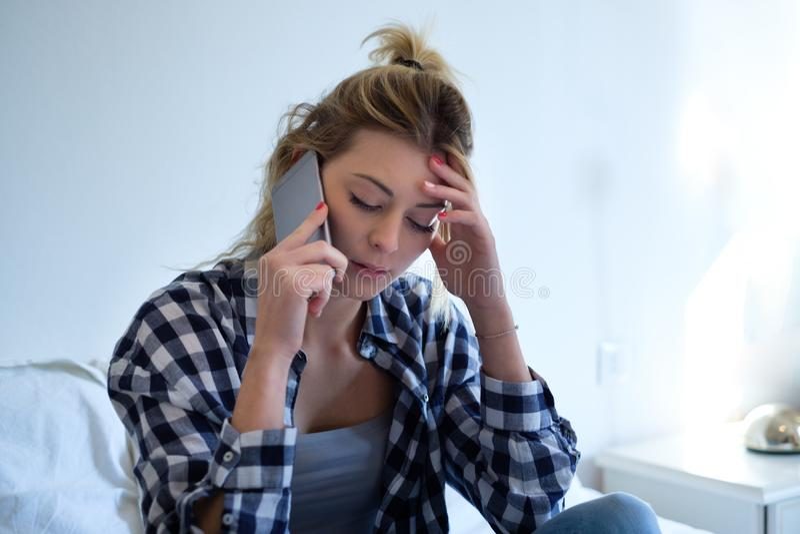由电话的女孩哀伤的听力坏消息 免版税库存照片