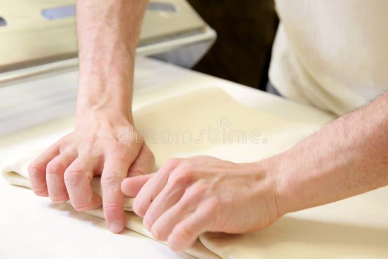 由男性手的铺开的面团在面包店 免版税库存照片