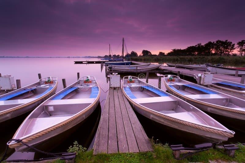 由码头的小船在日出期间的湖避风港 库存图片