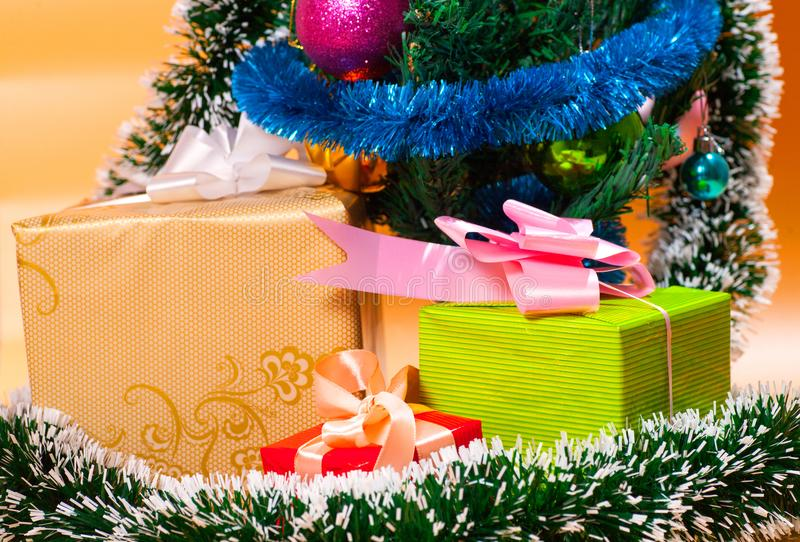 由礼物盒和土气圣诞节装饰做的生态圣诞树在与圣诞快乐的木背景 库存照片