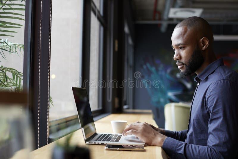 由窗口的中间成人黑男性创造性的开会在使用膝上型计算机的办公室社交范围,侧视图 免版税图库摄影