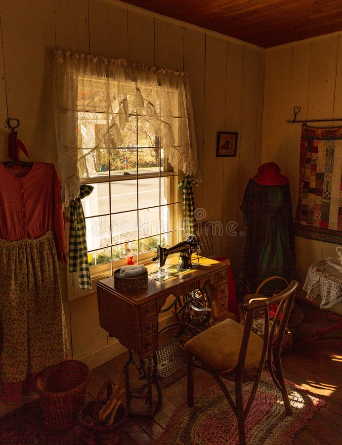 由窗口的古色古香的缝纫机与等候裁缝的坐的椅子 免版税库存照片