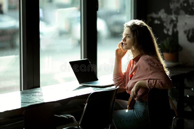 由窗口的女孩在咖啡馆 免版税图库摄影