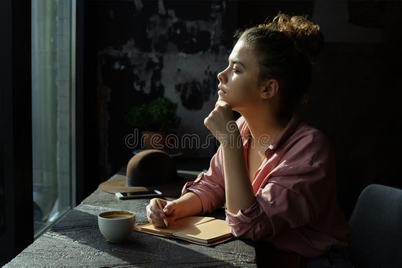 由窗口的女孩在咖啡馆 免版税库存照片