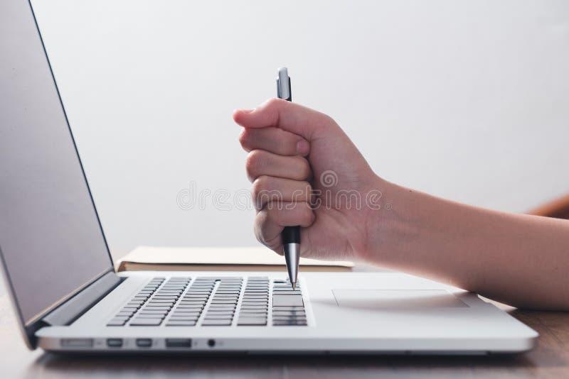 由笔的恼怒的妇女命中膝上型计算机 库存图片
