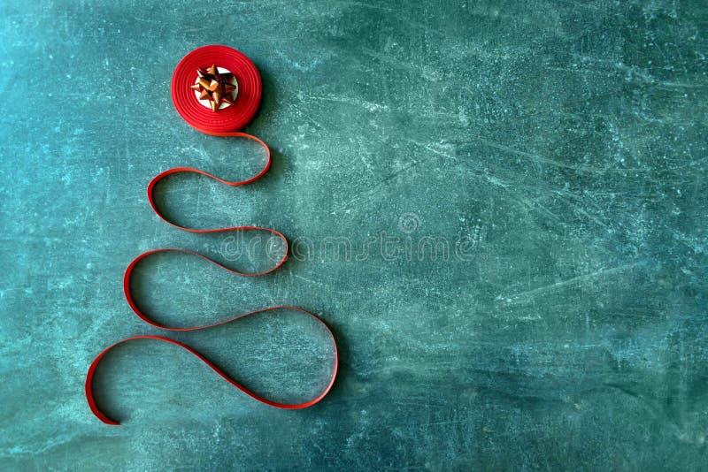 由红色卷曲丝带和红色弓做的装饰圣诞树 免版税库存图片