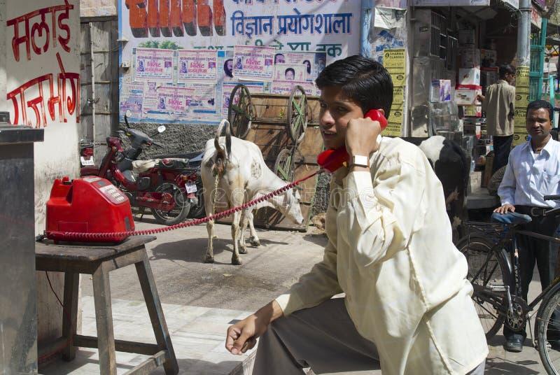 由红色街道商店的人电话打电话,乔德普尔城,印度 免版税库存照片