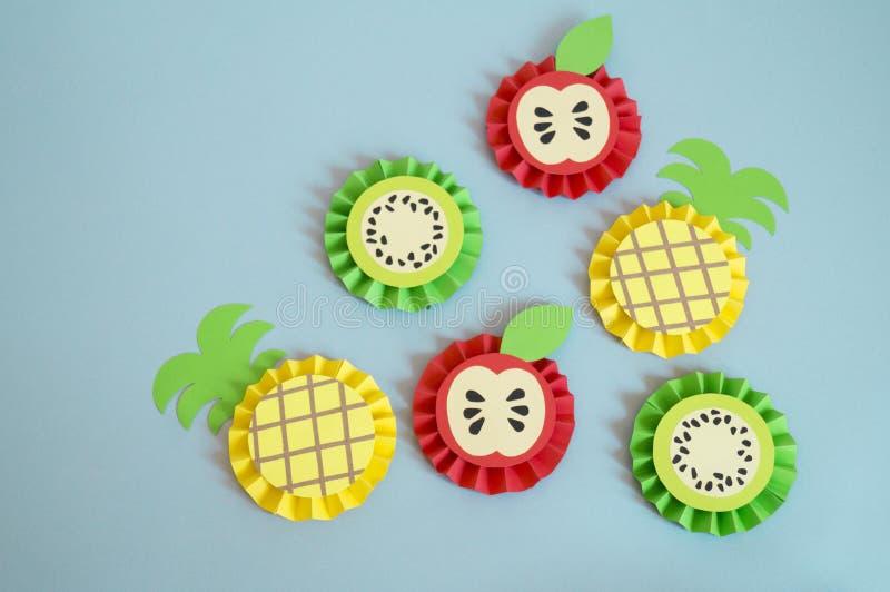 由纸做的果子在蓝色背景 菠萝,桔子,柠檬,西瓜,猕猴桃,苹果 库存图片