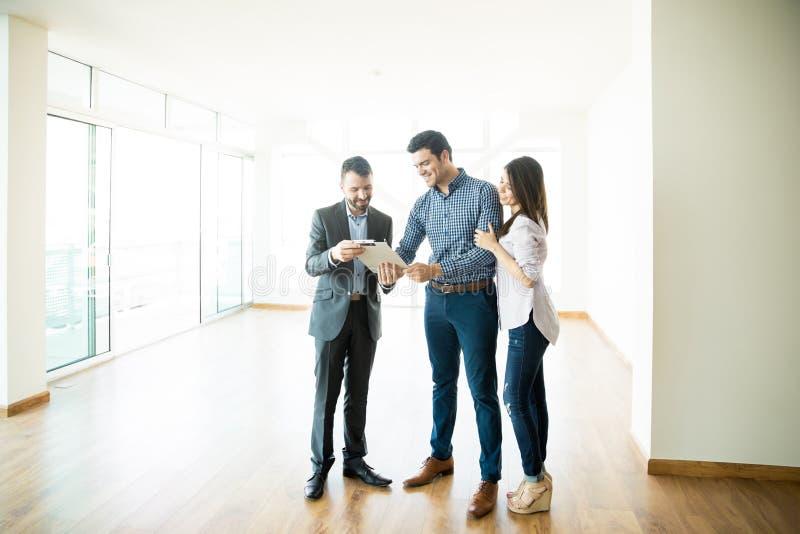 由经纪的夫妇签署的销售购买协议在新的家 库存照片