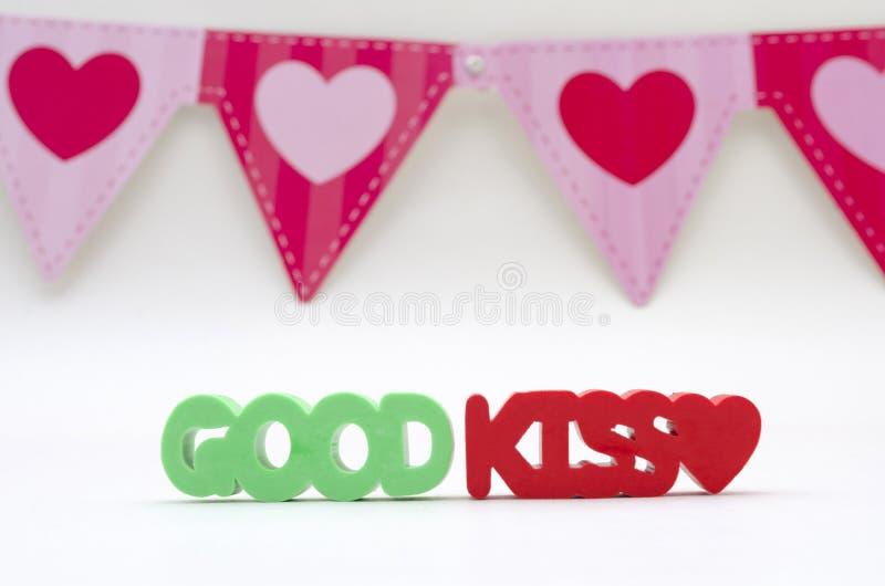 由绿色和红色橡皮擦做的好亲吻词组 库存照片