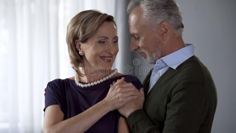 由肩膀的愉快的年迈的丈夫藏品妻子从后面,结婚纪念日 库存图片