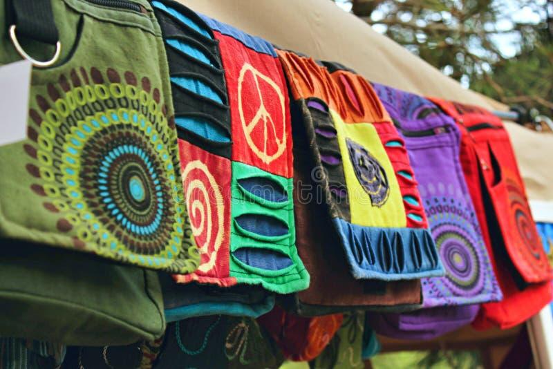 由自然材料做的漂泊袋子在衣裳在一个嬉皮的节日市场上站立 免版税库存照片