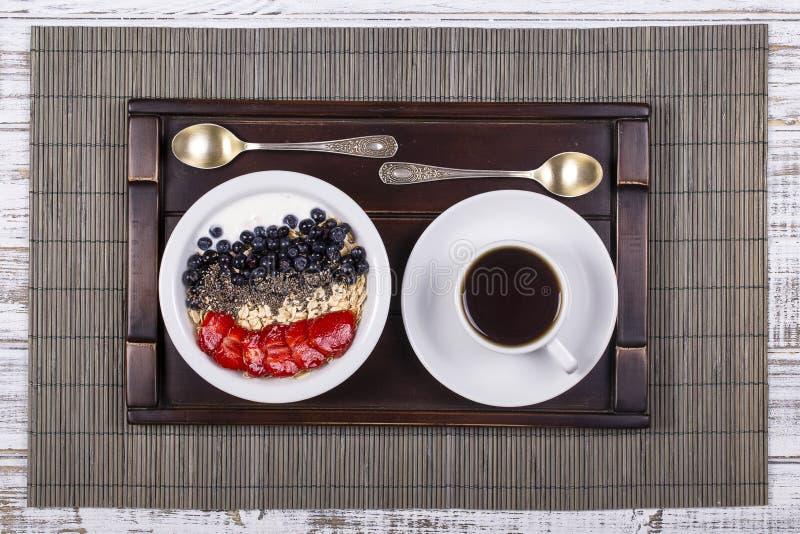 由草莓和健康muesli做白色咖啡,蓝莓, chia种子,燕麦剥落用在一个盘子的酸奶在白色木头 免版税图库摄影