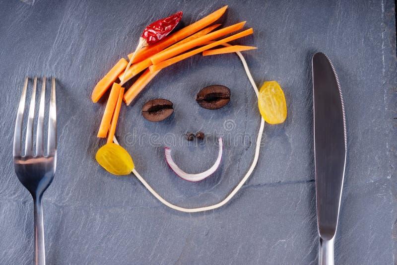 由菜、刀子和叉子做的兴高采烈的面孔 免版税库存照片