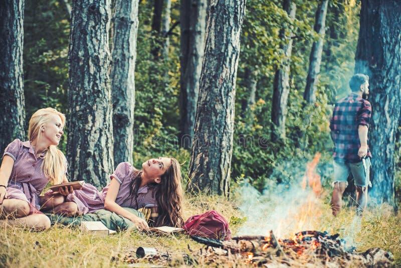 由营火的梦想的女孩看书 说谎在草的妇女 走入森林的人 库存图片