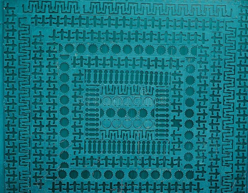 由蓝色油漆的不同的几何形状穿孔的铁破旧的板料Painte 库存照片