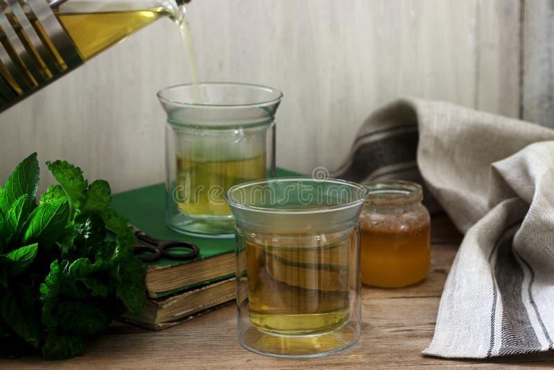 由薄菏和香蜂草做的清凉茶用在玻璃杯子的蜂蜜 r 图库摄影