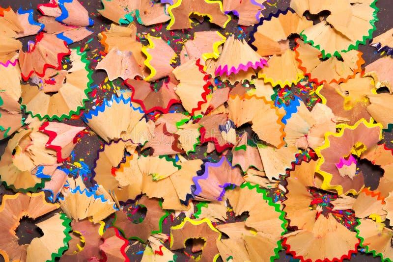 由蜡笔做的五颜六色的磨削器削片被安排作为背景 免版税库存照片