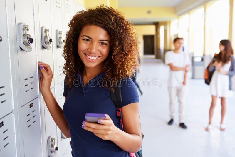 由衣物柜的女性高中学生使用手机 免版税库存图片