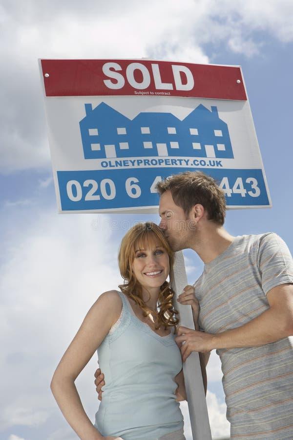 由被卖的标志的愉快的夫妇反对天空 免版税库存图片