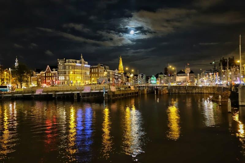 由被阐明的都市风景的河反对在黄昏的天空 图库摄影